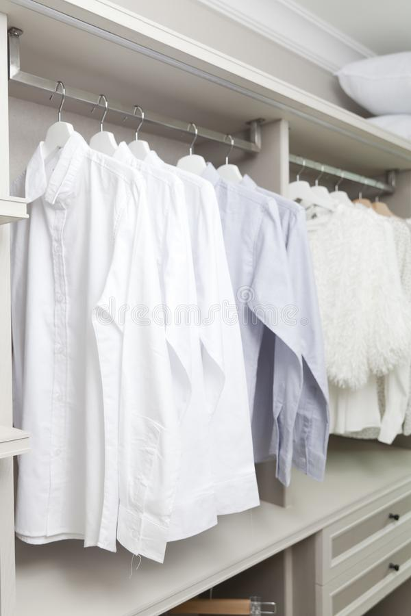 Cloths hanging in wooden wardrobe at home stock photos