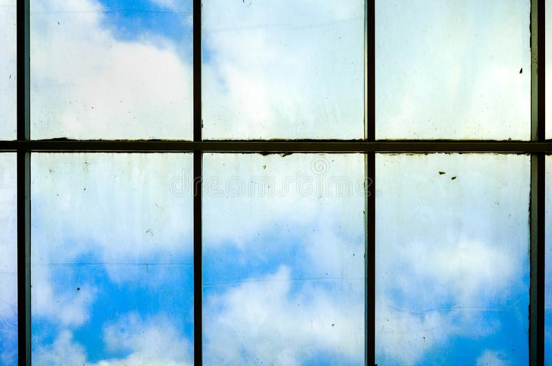 Cloud Behind A Very Dirty Dim Windows Full of Dust Dirt and Mildew That Need To Be Clean at The Top of High Rise Building. Or Skysrapper. From Inside Looking royalty free stock photography