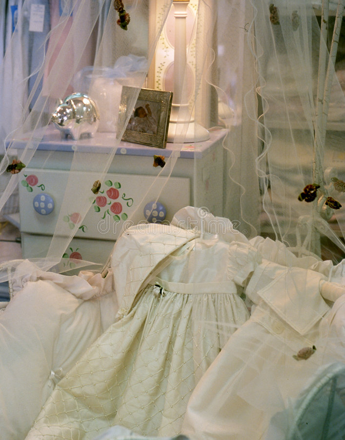 Cloud clothes. White baby clothes laying on a crib with sheer drapes stock photography
