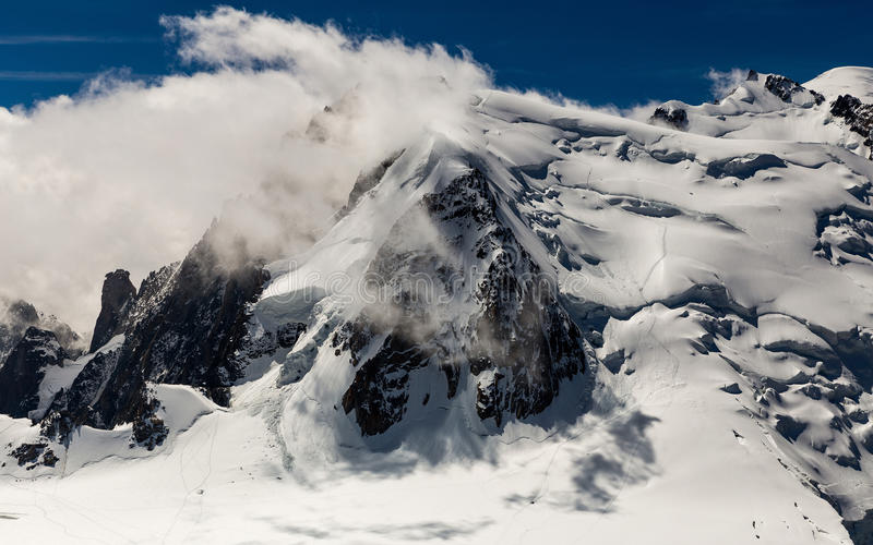 The cloud clung to the mountain with the hanging of an avalanche. royalty free stock photography