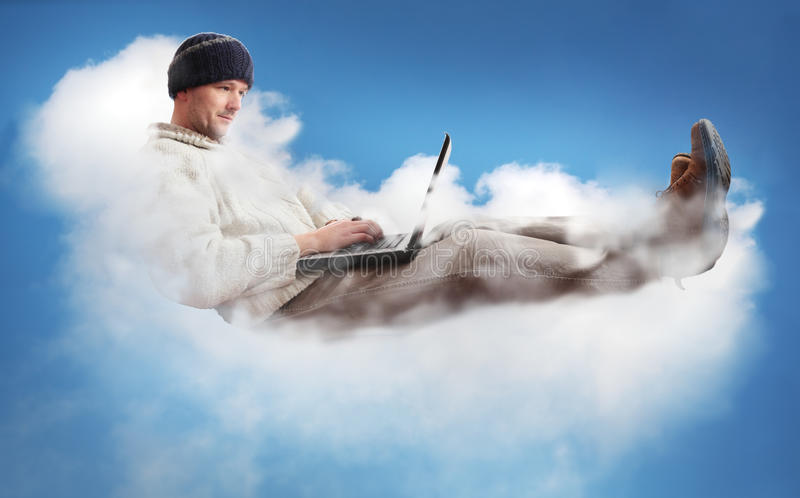 Cloud Computing. A man on a cloud operating a laptop. The man is dressed casually to represent the majority of IT workers. The concept is Cloud Computing royalty free stock photography