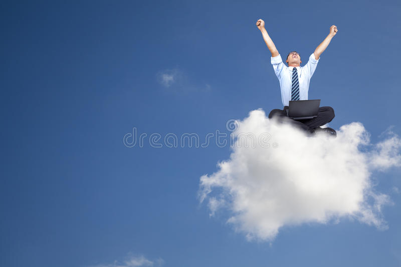 Cloud computing concept. Young businessman with computer sitting on the cloud