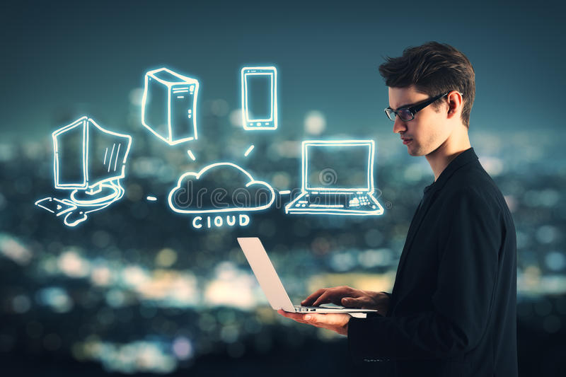 Cloud computing concept. Side view of handsome young businessman using laptop with abstract computer icons on blurry night city background. Cloud computing royalty free stock image