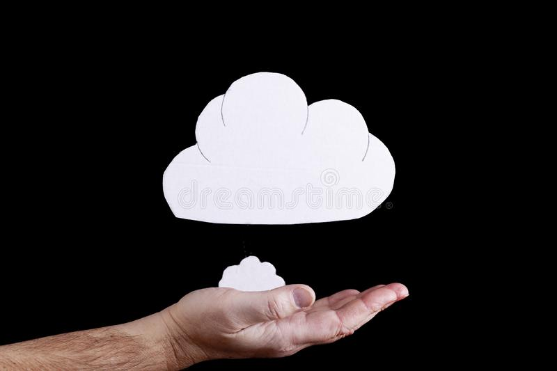 Cloud concept with open hand on black. Cloud concept with cardboard cloud cutouts floating above an open hand on a black background royalty free stock image