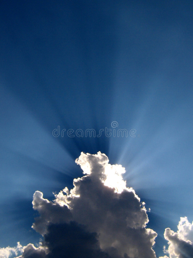 Cloud Cover. A cloud cover the sun creating a beautiful spectacle of sunrays in the blue skies at the arrival of monsoon season in India royalty free stock photos