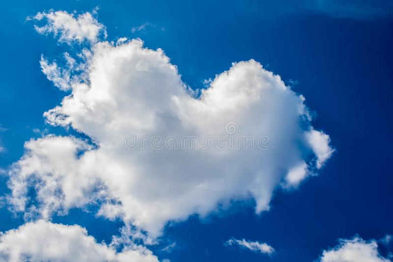 The cloud in the form of heart against a blue sky. To the Valentine`s Day stock images