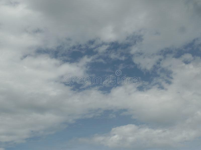 Cloud formations in the sky. White pockets of cloud formations in the sky obscuring the blue background royalty free stock photo