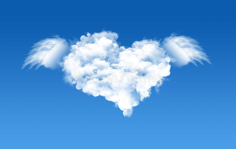 Cloud heart shape in the blue sky. A heart shaped cloud formation against clear blue sky and flying with wings stock photo