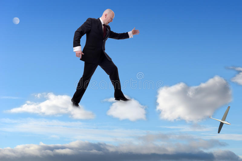 Cloud hopping. A businessman stepping on clouds royalty free stock images