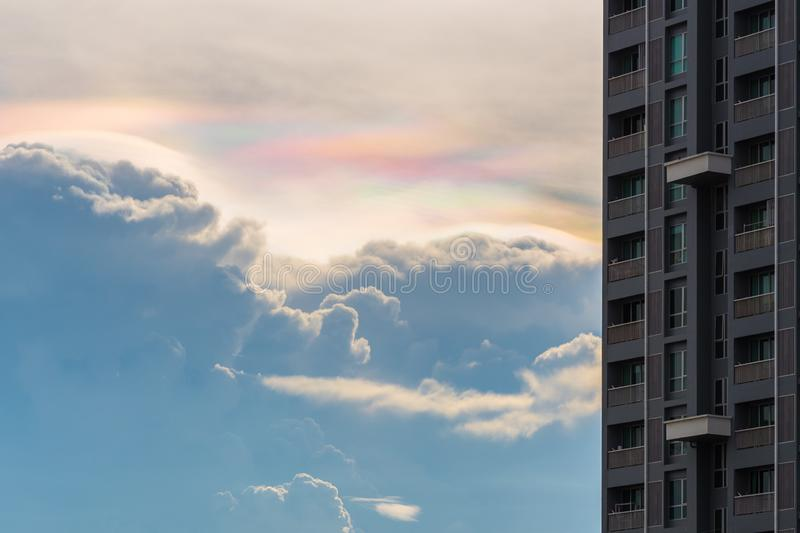 Cloud iridescence cloud in rainbow colors with a high-rise building in Bangkok royalty free stock photography