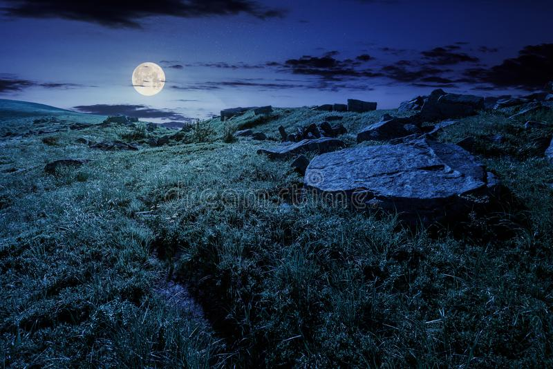 Cloud over the grassy hillside with rocks at night stock image
