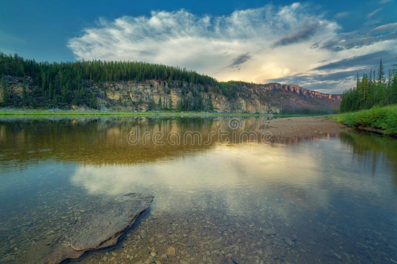Cloud over the rocky bank of the taiga river River Amga. stock image