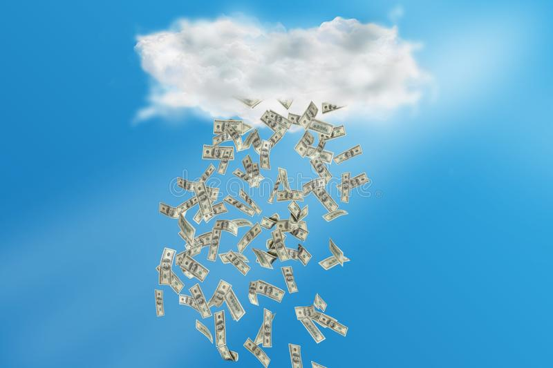 Cloud with Rain of Money. Composite image of cloud with rain of money with bright blue sky on the background stock image