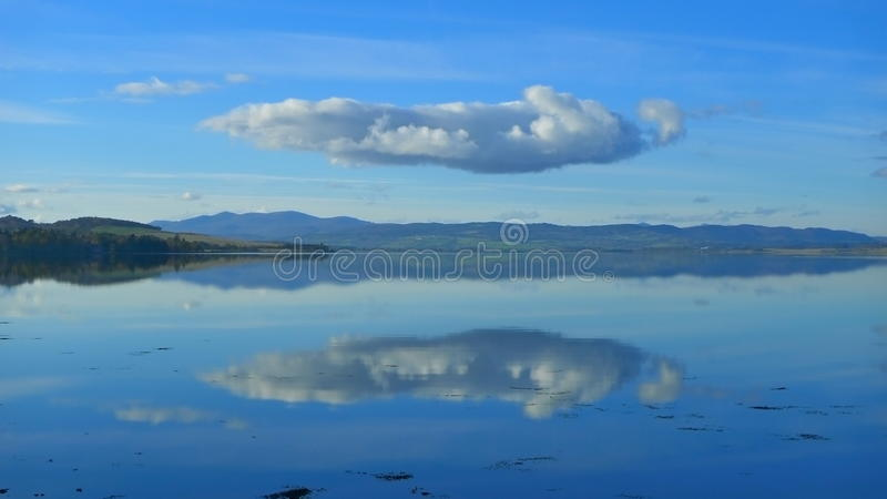 Cloud reflected in sea stock photo