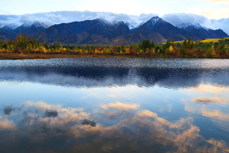 Cloud reflections in smooth water surface, autumn forest and mountains stock photos