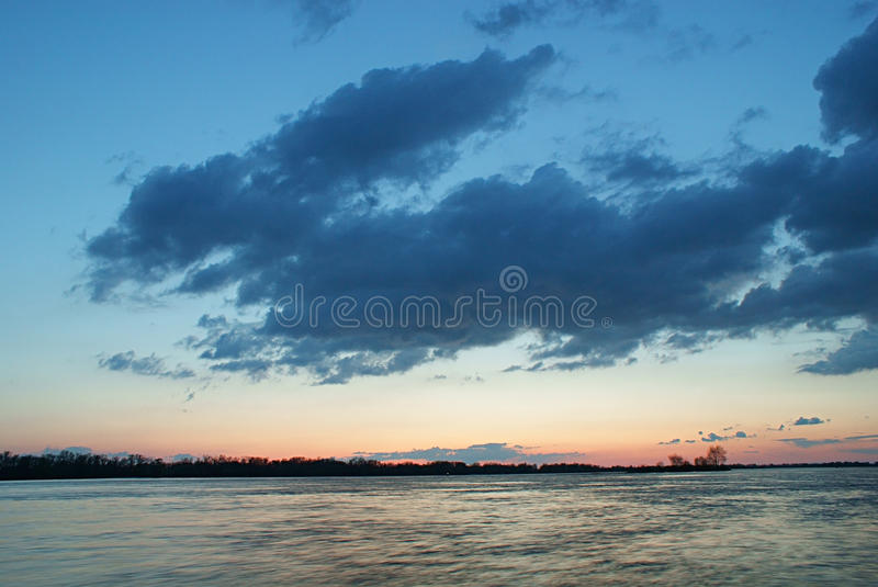 Cloud shape of animal above a river at sunset. A large cloud in blue sky of shape of running animal of hare above wide river with rapid current at sunset with stock images