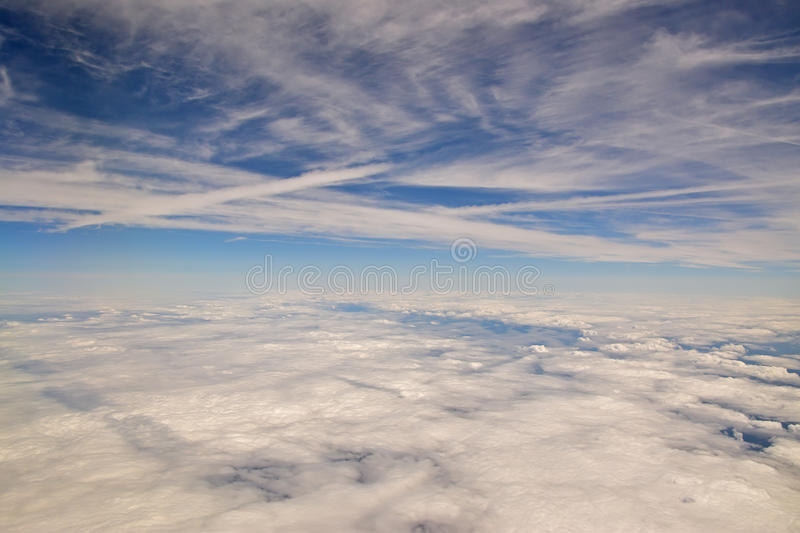 Cloud in the sky. Layers of cloud in the blue sky viewed from within an aircraft stock image