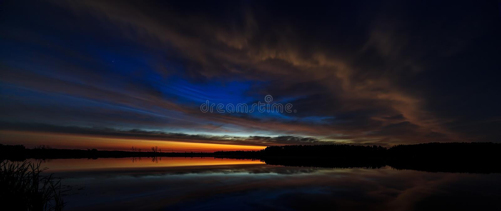 Cloud in the sky lit morning dawn, reflected in the water. Of the lake royalty free stock image