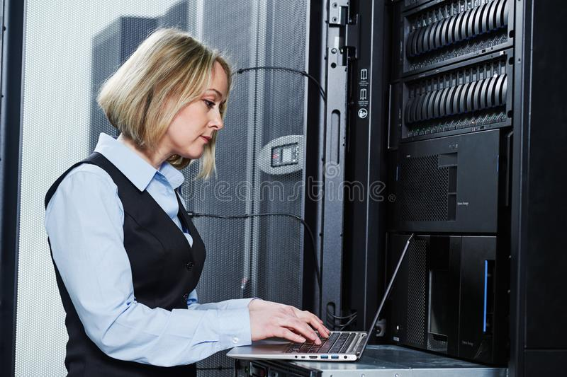 Cloud storage service. female engineer works with laptop in data center stock photo