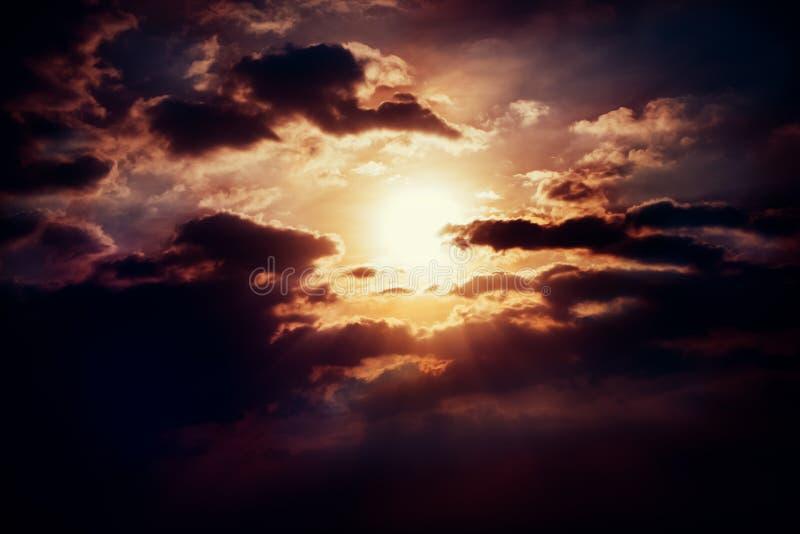 Cloud texture in sky. Sun behind cloud with rays in dark sky stock photos