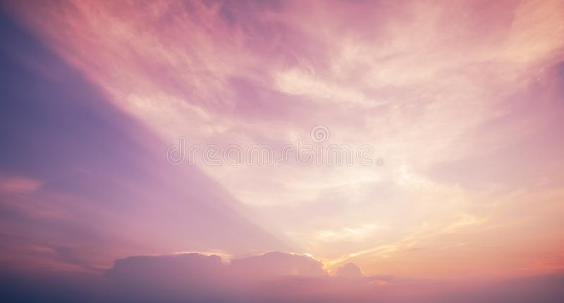 Cloud texture in sky. Sunset behind cloud with rays in pastel sky royalty free stock image
