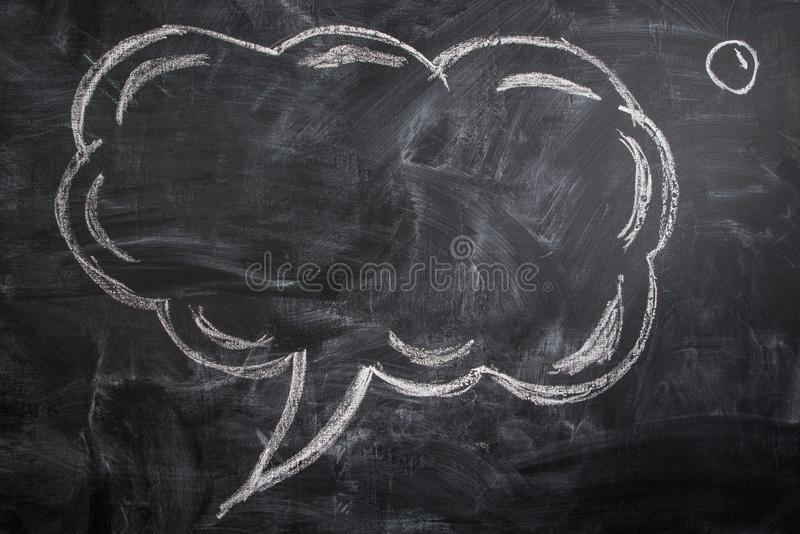 Cloud thought sketched on a chalkboard. Cloud thought sketched on a black chalkboard royalty free stock image
