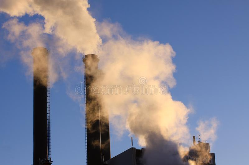 Cloud of white smoke from industrial chimney against blue clear sky with copy space. For writing stock photography