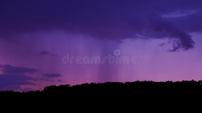 Cloudburst. A moody shot of a cloudburst above a forest royalty free stock photo
