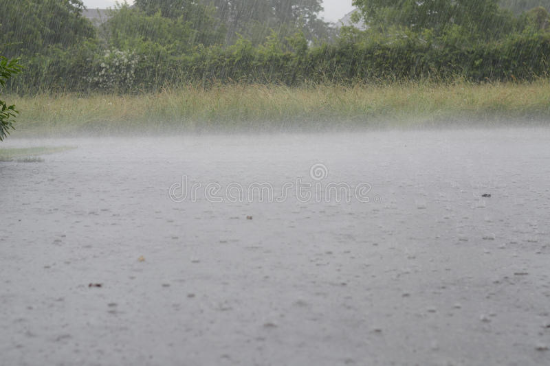 Cloudburst on the street. Heavy rainfalls burst into the street during a thunderstorm royalty free stock images