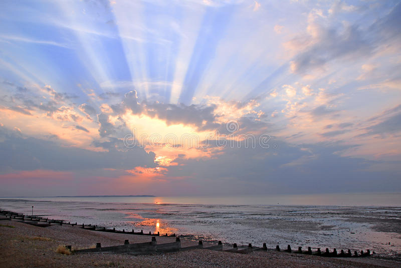 Cloudburst sun rays sunset. Photo of a beautiful kent sunset over whitstable bay with sun rays bursting through the clouds stock photo