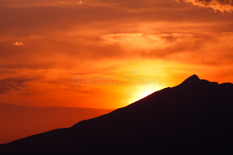 Clouded orange sky with mountain silhouette royalty free stock images