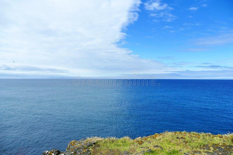 Cloudfrount que crea diversas sombras del azul en el mar islandés fotos de archivo