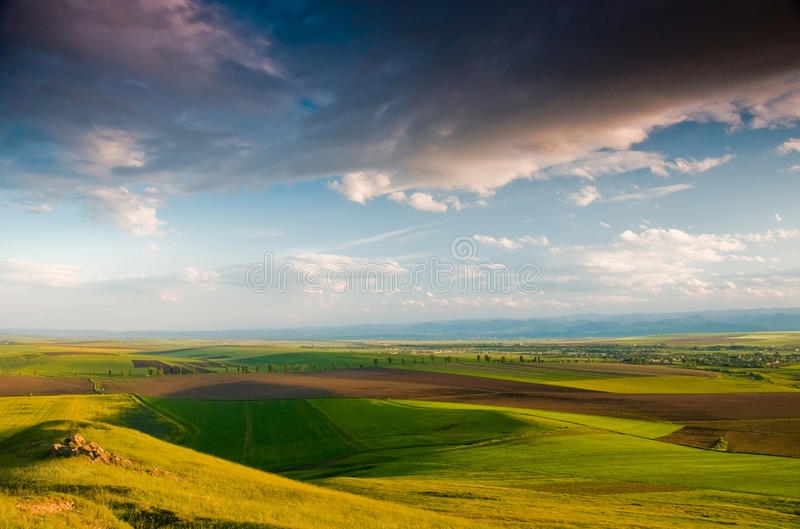Clouds over blue sky and green agriculture field stock photography