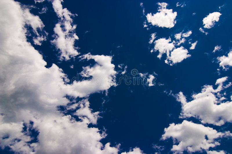Clouds. Beautiful big white clouds in front of dark blue sky background stock photography
