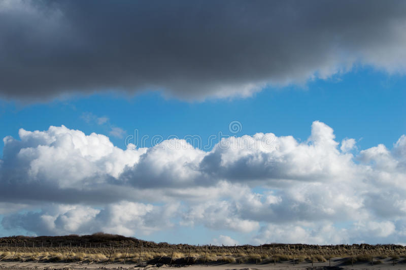 Clouds in a beautiful cloud formation above the dunes royalty free stock photography
