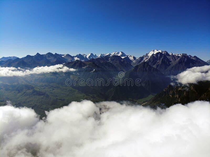 clouds berg över maxima Dimma i de Kaukasus bergen royaltyfri fotografi