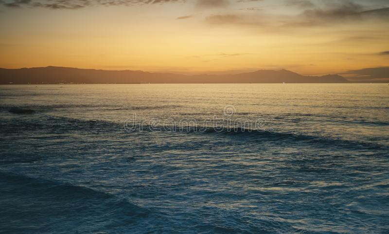 Clouds blue sky and gold sunlight sunset on horizon ocean, background seascape dramatic atmosphere rays sunrise. Relax view waves stock photography