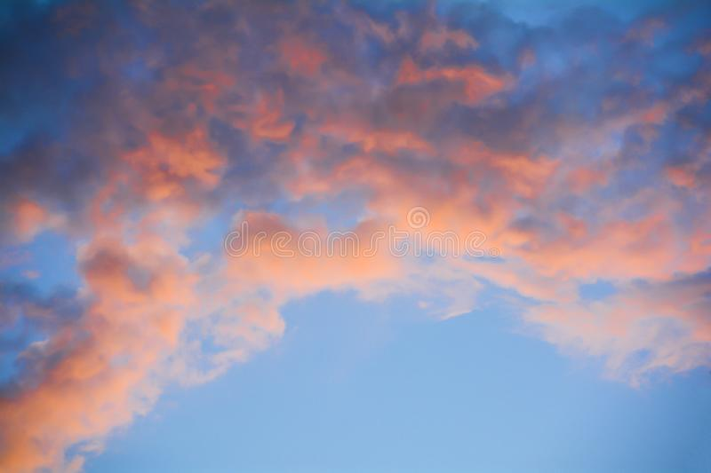 The clouds in the blue sky are illuminated by the orange setting sun. Natural background royalty free stock photo