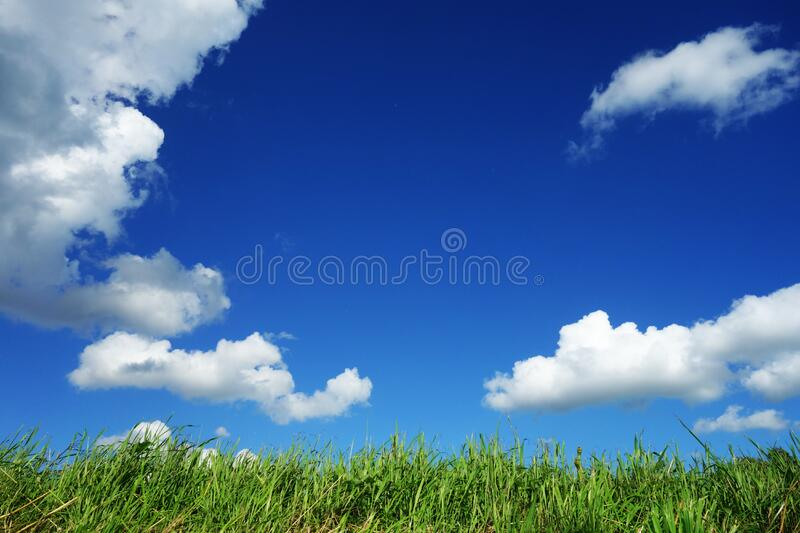 Clouds in blue sky over field stock photography