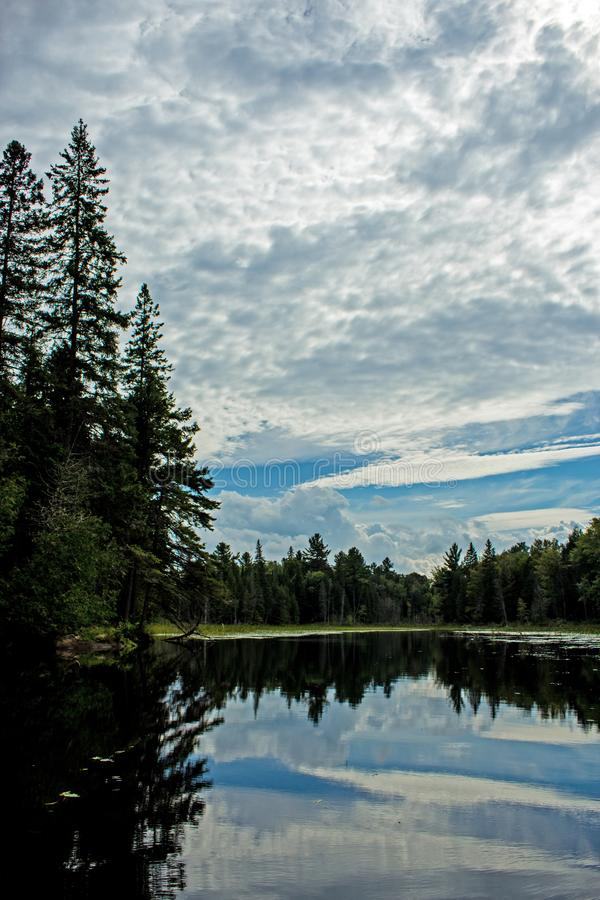 Clouds and Blue Sky Reflected In Calm Water. Clouds mixed with blue sky and some riverside trees are reflected in the calm waters. Location is on Nogies Creek in stock images