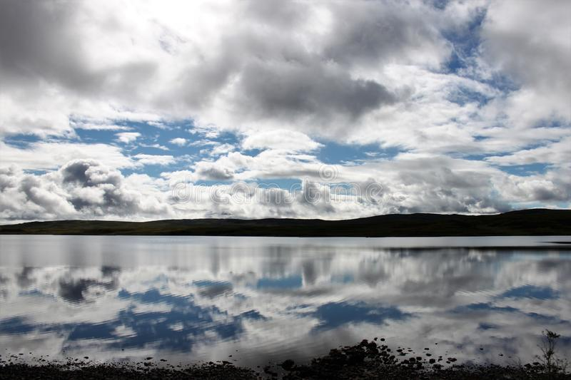 Clouds and blue sky reflected in a Scottish loch. Blue sky and white clouds reflected in a Scottish lake royalty free stock photos