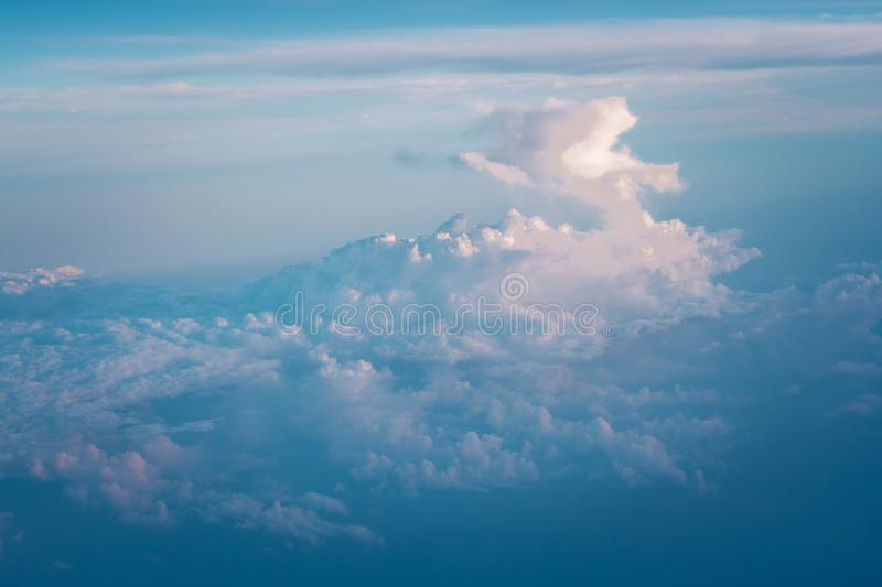 Clouds and blue sky view out from window of airplane flying over earth ground. stock image
