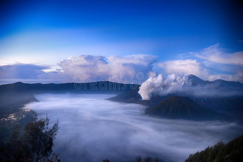 Clouds in the caldera of Bromo volcano at dawn. Against the background of a volcanic erupting smoke royalty free stock photography