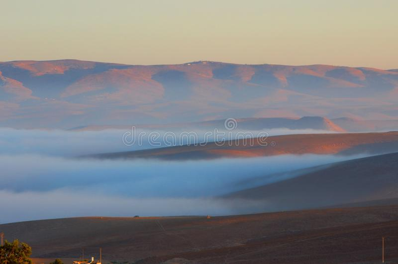 Clouds coming on the red mountains during sunrise in Arad city Israel royalty free stock photography