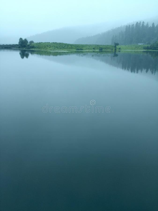 Clouds covered the mirror-like surface of the blue lake royalty free stock photos