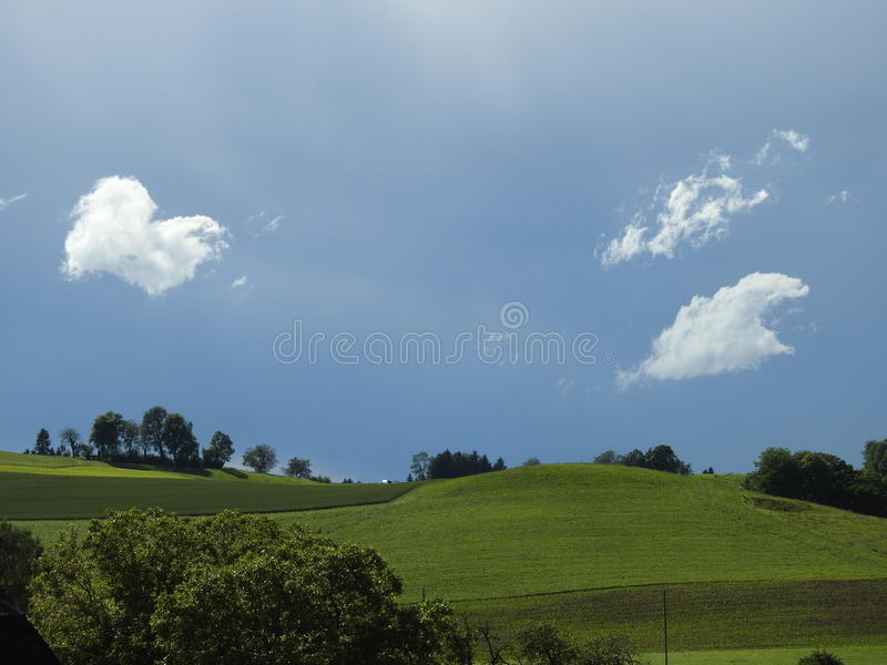 Clouds dance over hills stock image
