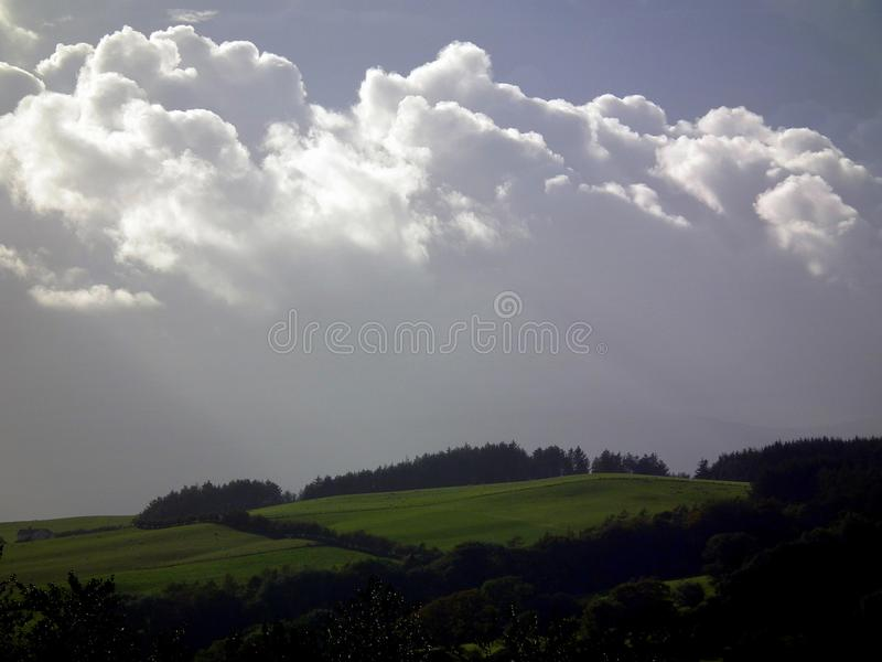 Clouds at dusk. White cumulus clouds high over rich farmland, at dusk/early evening royalty free stock image