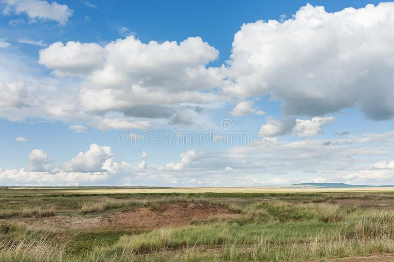 Clouds float across the sky over meadows. Tyva. Steppe. Sunny summer day royalty free stock image