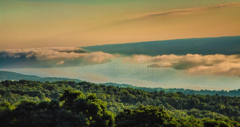 Clouds Float Over A Hazy Valley. Beautiful long clouds drift over a valley shrouded in mist as the sun begins to rise over the distant hills royalty free stock images