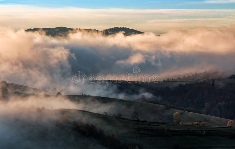 Clouds and fog rising over countryside. Rural fields on hills in gorgeous autumn sunrise stock photo